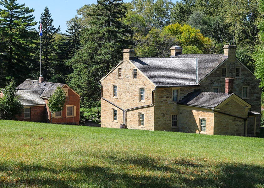 A large stone house set back in a field next to a cabin.