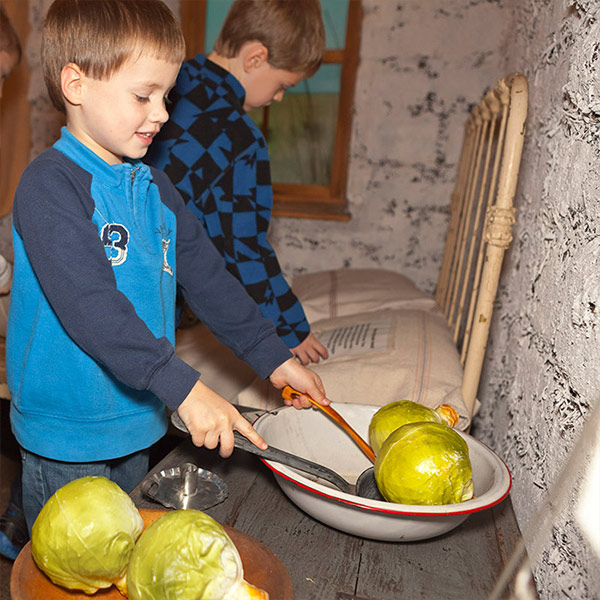 A boy spoons pretend cabbage out of a bowl in the sod house.