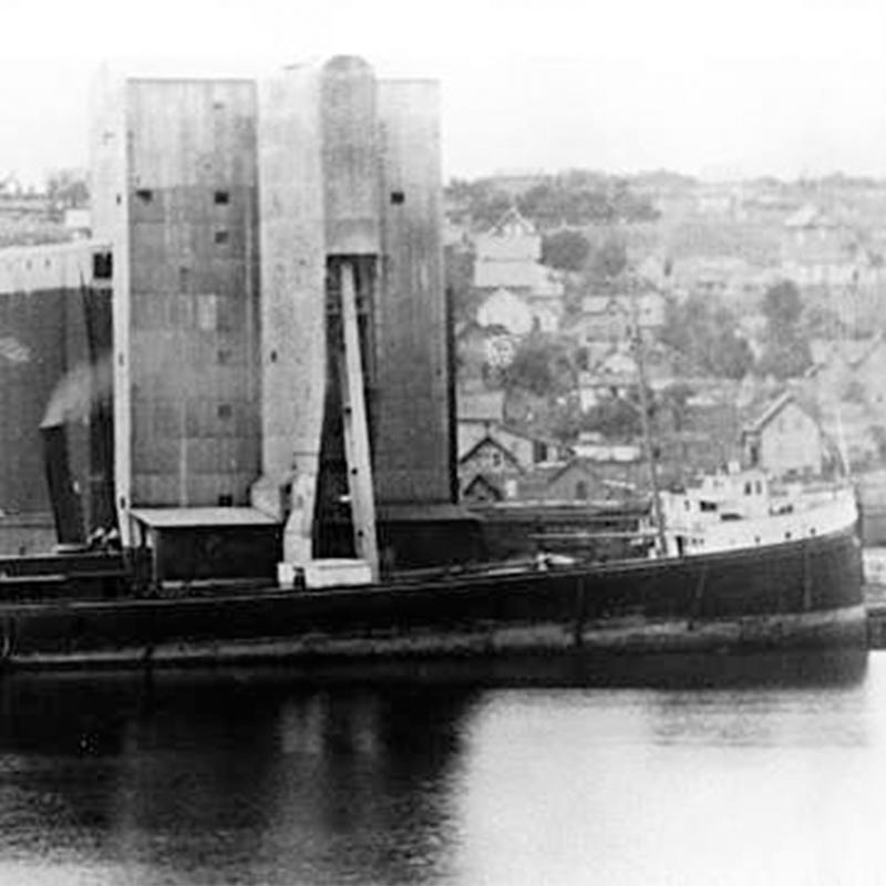 View of the George Spencer at port, taken from sea so the land is in the background