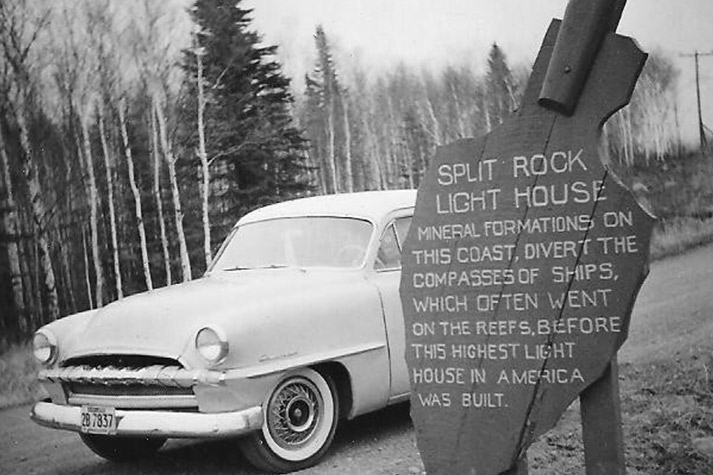 Old car next to a sign: Mineral formations on this coast divert the compasses of ships, which often went on the reefs, before this highest light house in America was built