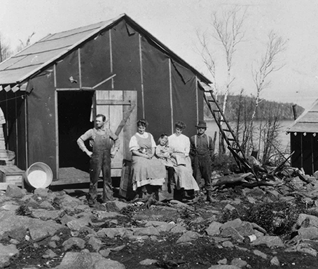 Men women and children in front of storage shed on rocky cliff