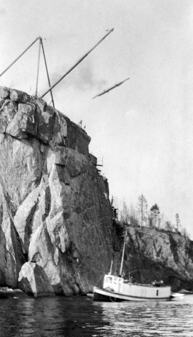 Hoist and derrick on top of rocky cliff above ship in Lake Superior