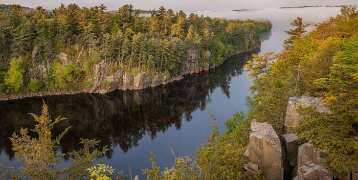 St. Croix river flowing through a valley of trees in early fall.