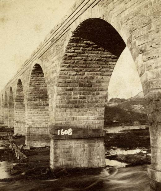 A stone bridge spanning the Mississippi river. See more historic photos of the Stone Arch Bridge.
