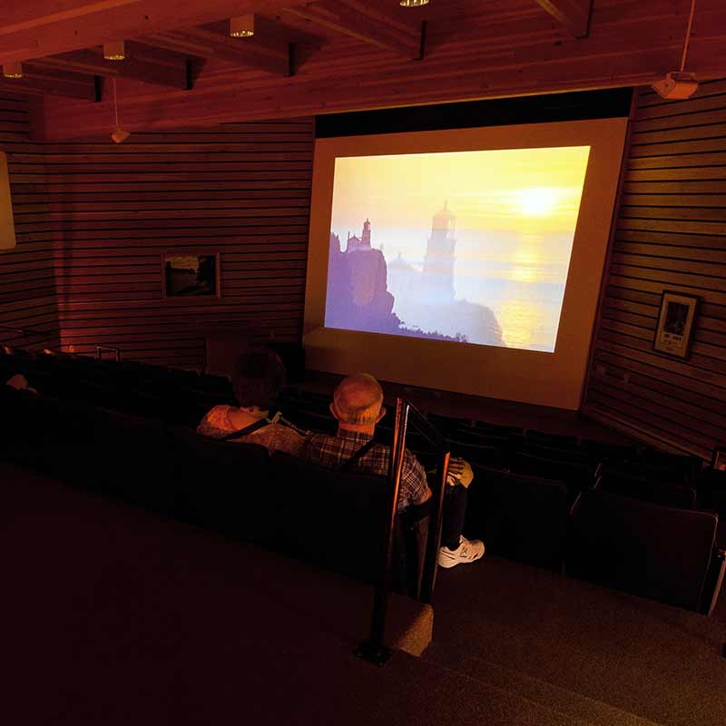 A couple sitting in a small theater watching a film projected onto a screen
