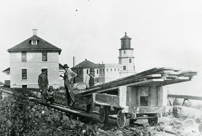 Men working on rail tracks with the lighthouse in the background