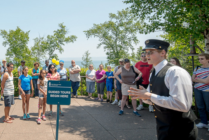 Tour guide dressed in lighthouse keeper uniform addressing a large group