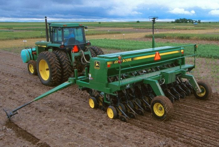 John Deere tractor with planter in a dirt field