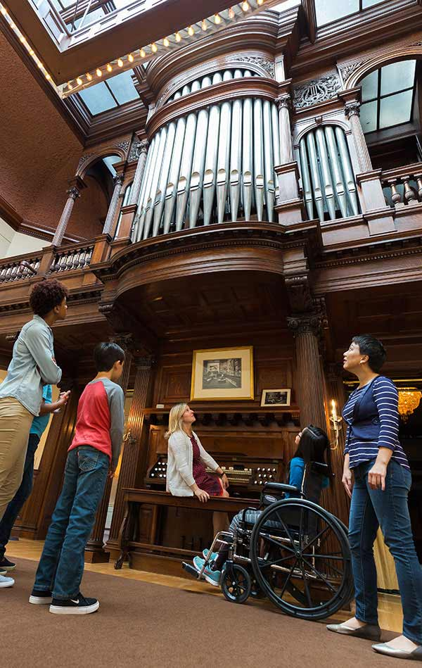 Woman sitting at large pipe organ with people looking up at the pipes