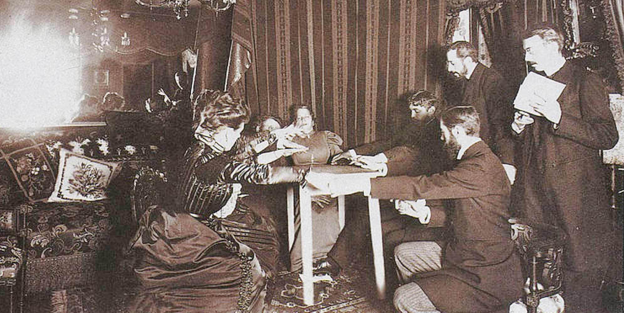 An old black-and-white image of four women and two men with their hands on a table