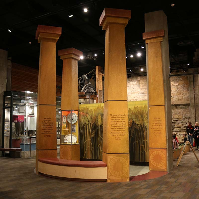 Wheat emporium sculpture with four large columns inscribed with text.