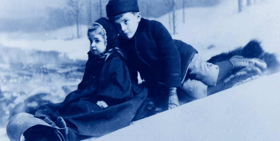Little boy and little girl riding on a toboggan