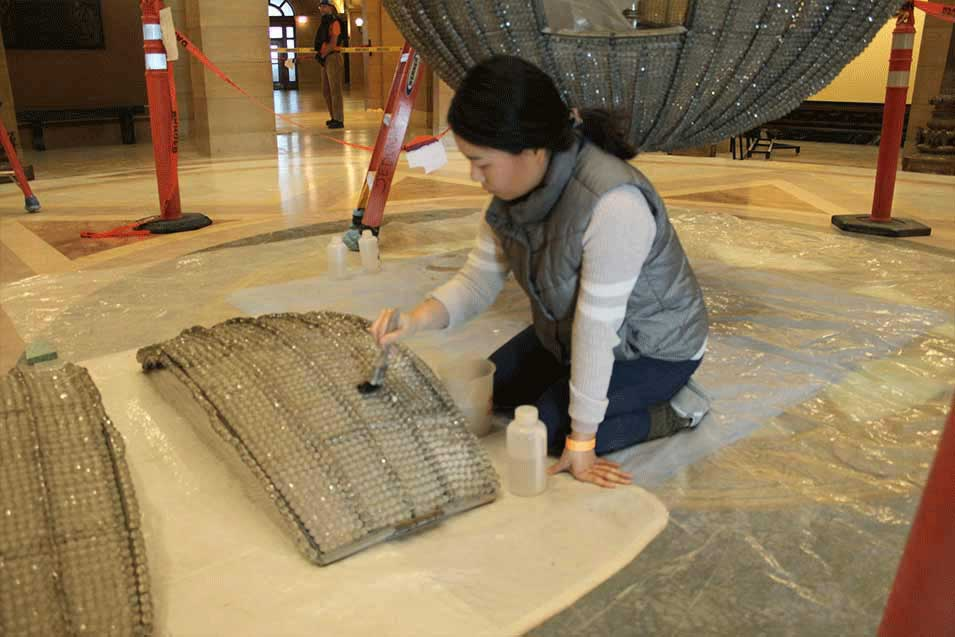 Woman cleaning pieces of chandelier.