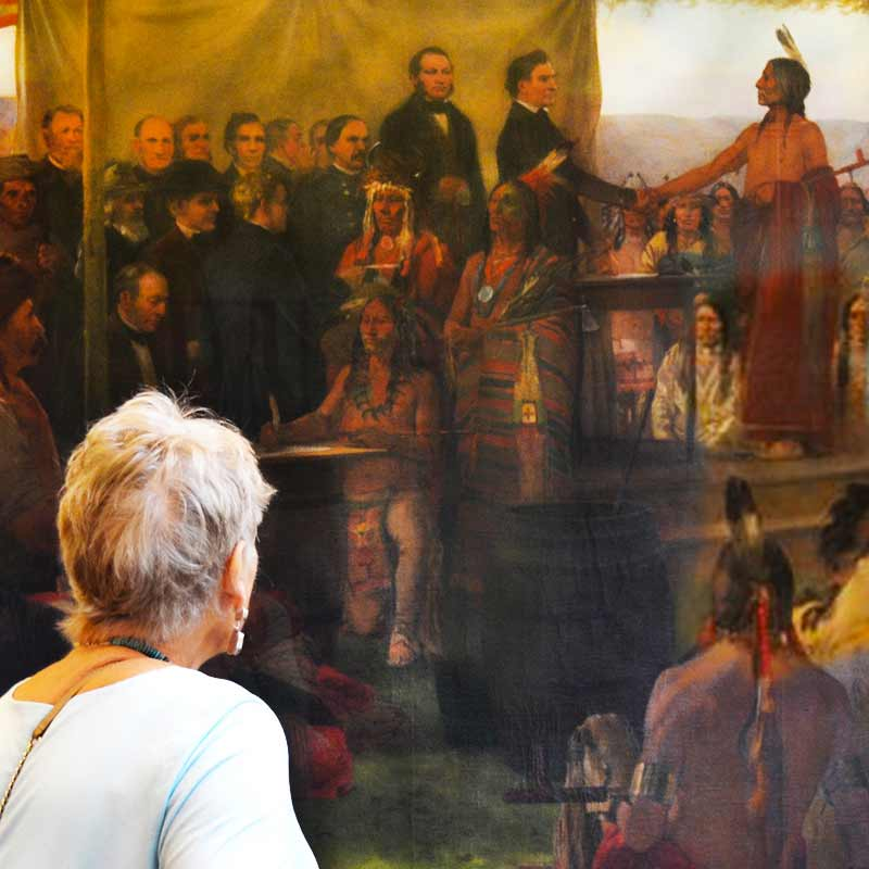 A woman looking at the Treaty of Traverse des Sioux painting