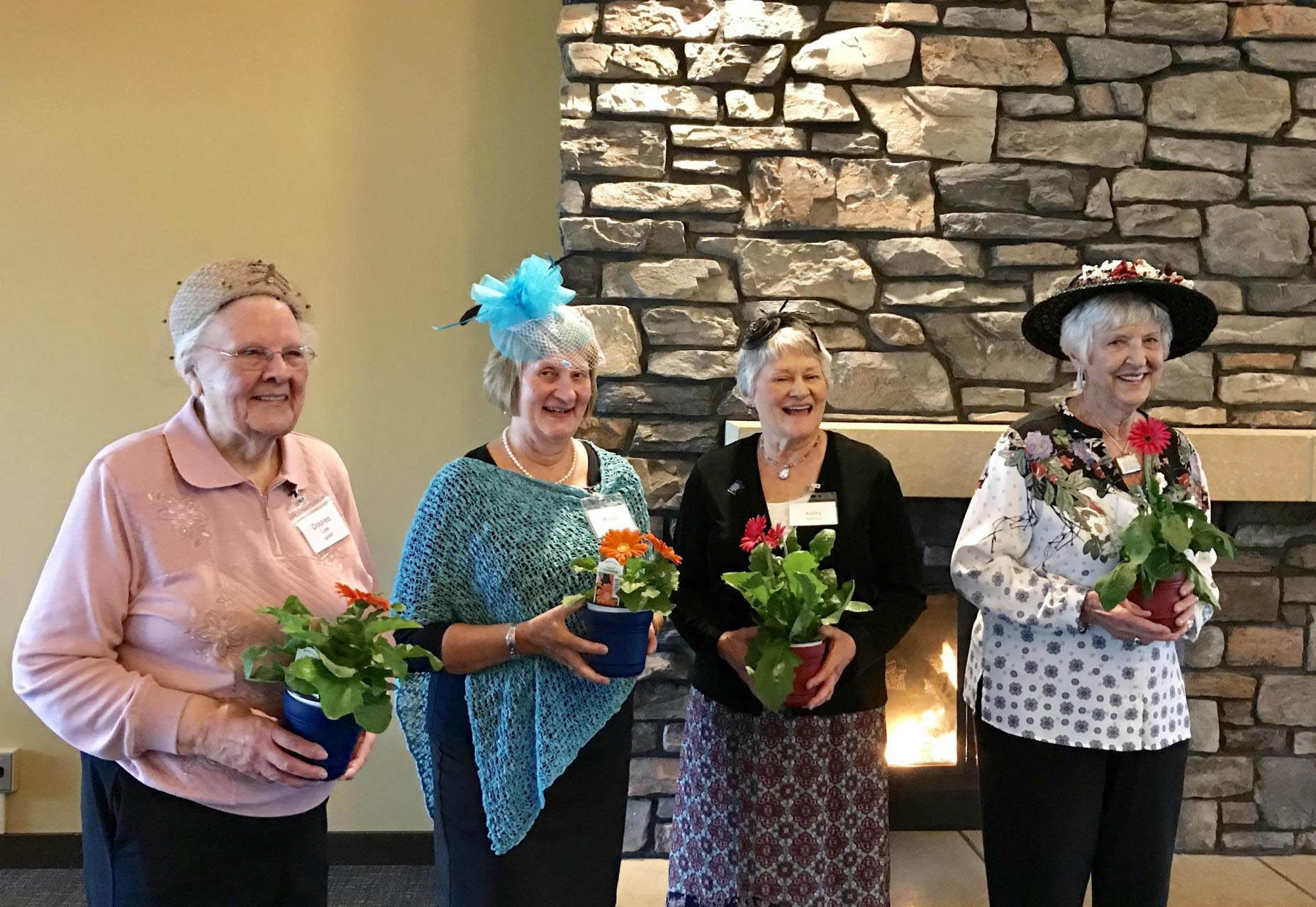 Four women wearing fancy hats and holding potted flowers.