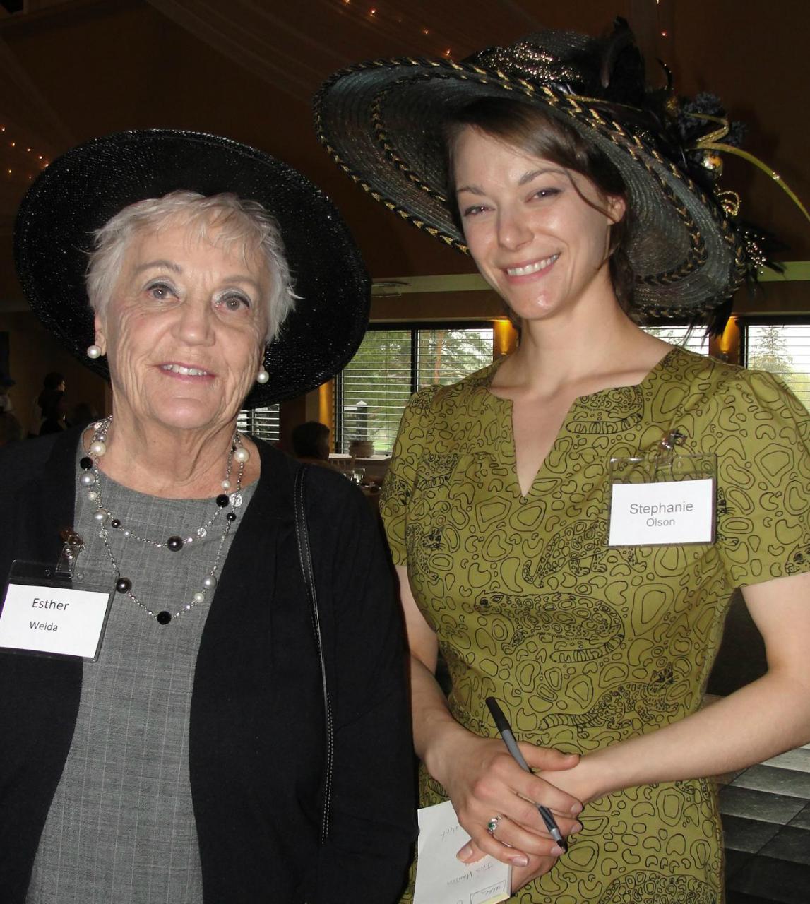 Two women wearing fancy hats.