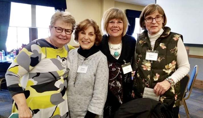 Four women smiling.
