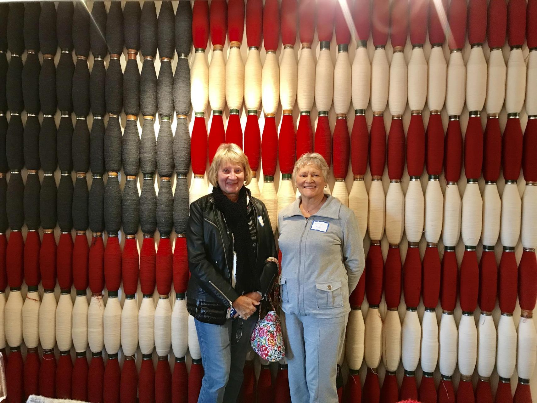 Two women standing in front of spools of yarn.