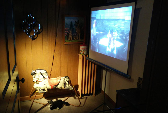 A projector screen shows home movies.