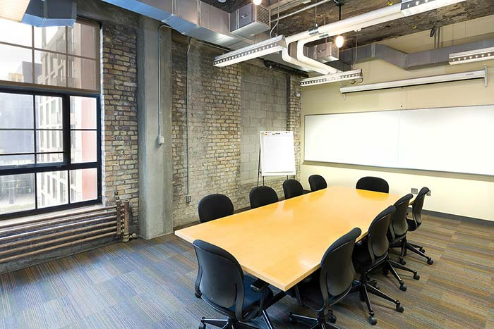 Room with exposed stone walls, a 10-person board room table, a white board, and industrial windows.
