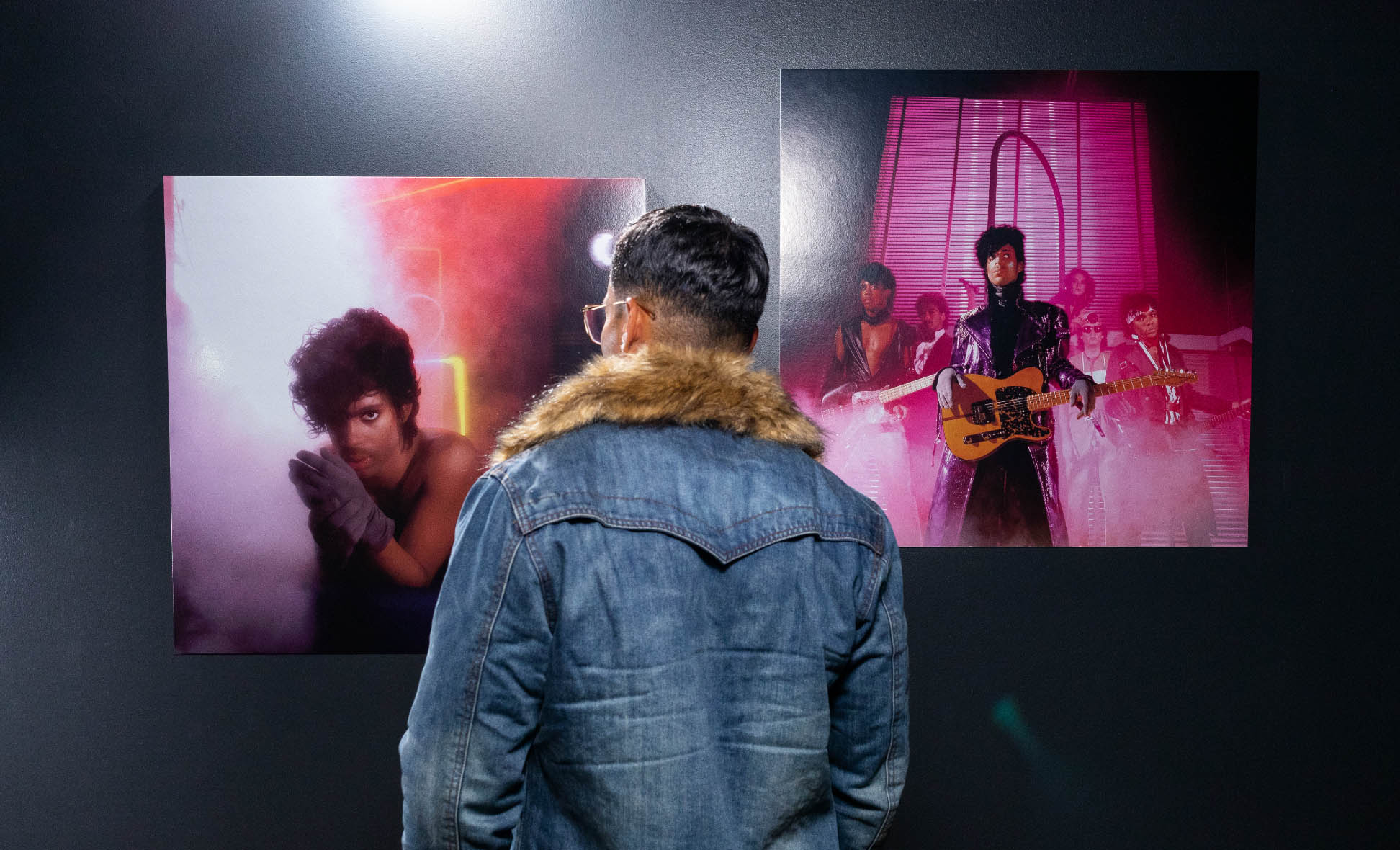 Man looking at photos in Prince Exhibit.