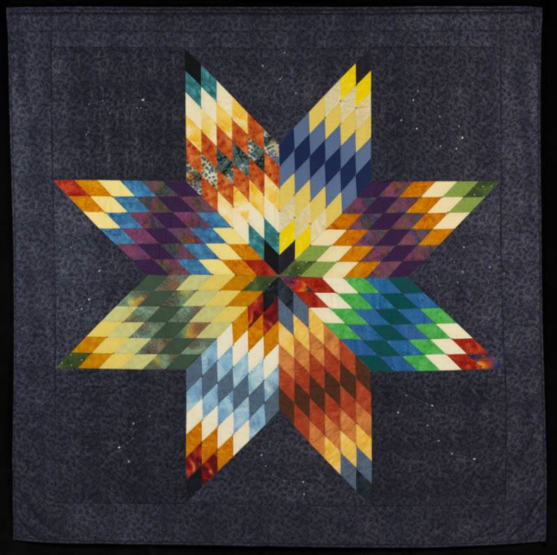 Quilt with multi-colored star pattern.