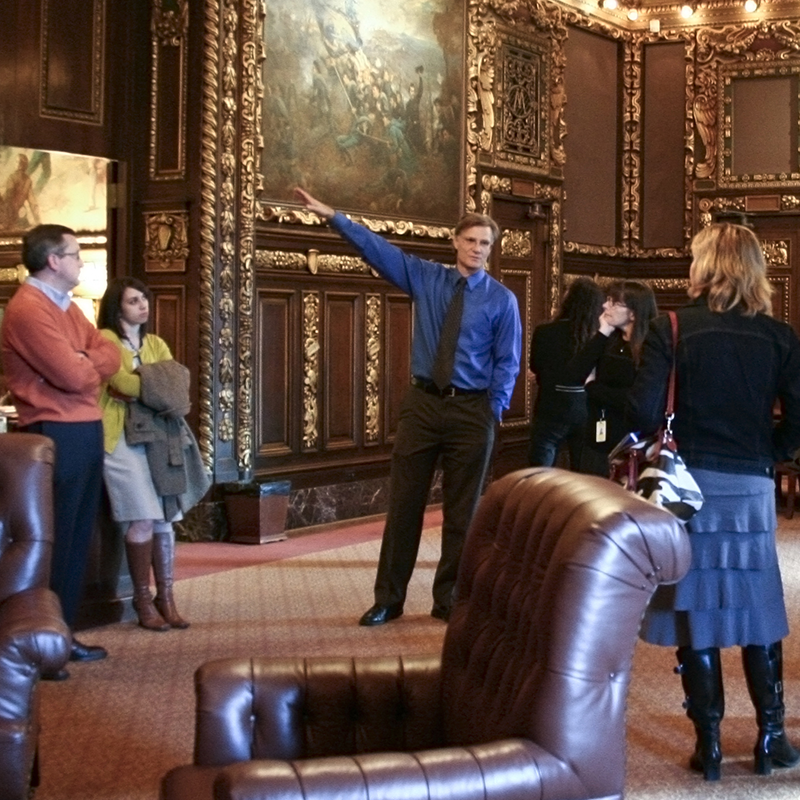 A tour guide pointing at a painting