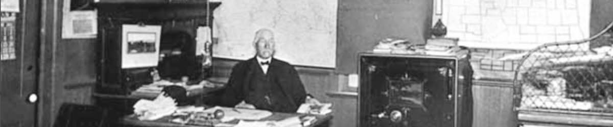 An old man in suits sitting behind a desk, black and white photo.