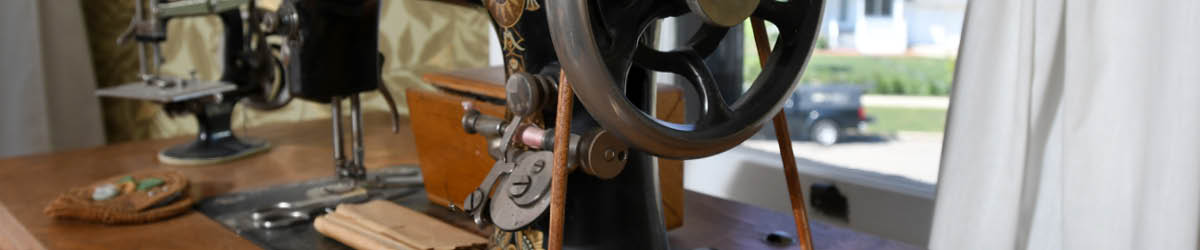 A close-up on the handwheel of a classic sewing machine.