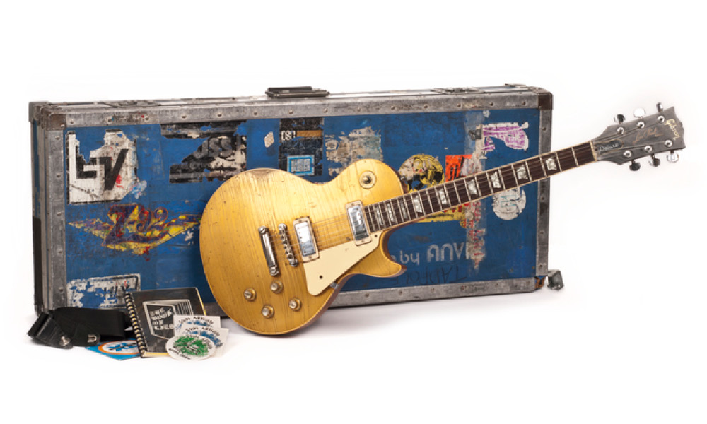 Gibson Les Paul gold-top six-string electric guitar with strap and case.