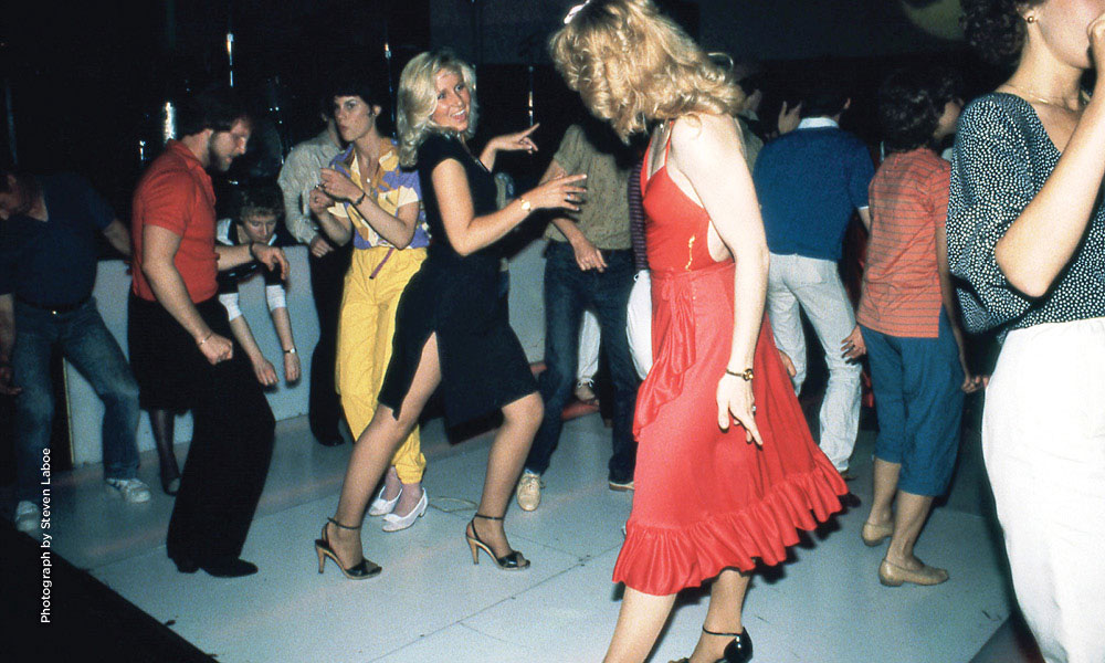 Woman in red dress in foreground, people disco dancing in background.