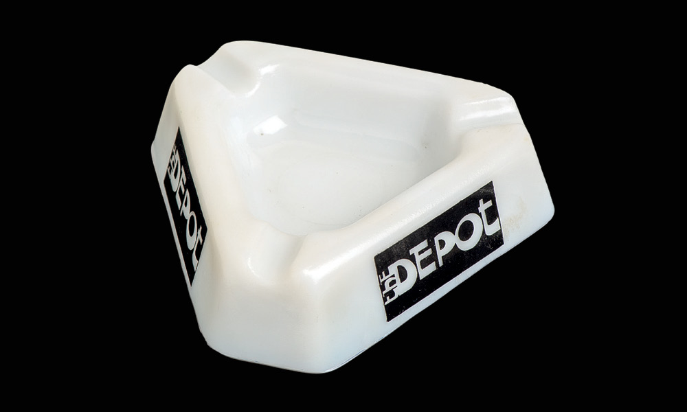 White triangular ashtray with The Depot logo in black on the side.
