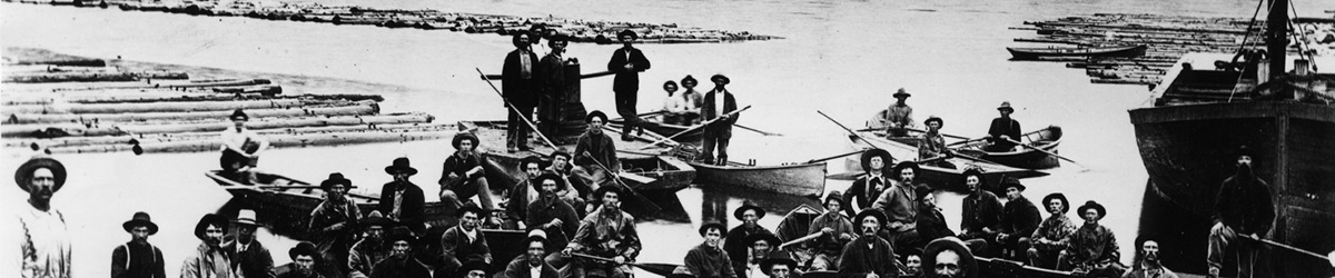 Lumberjacks on boats looking at the camera direction, black and white photo.