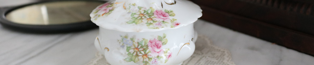 A ceramic container with flowers printed on the body and lid.