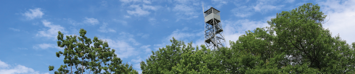 Looking up towards the 100-foot fire tower against a blue sky.