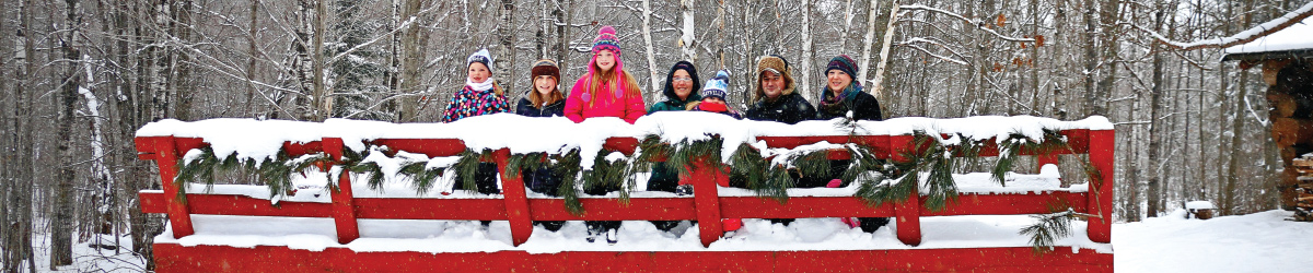 7 people on a big red snow covered sleigh in front of woods.
