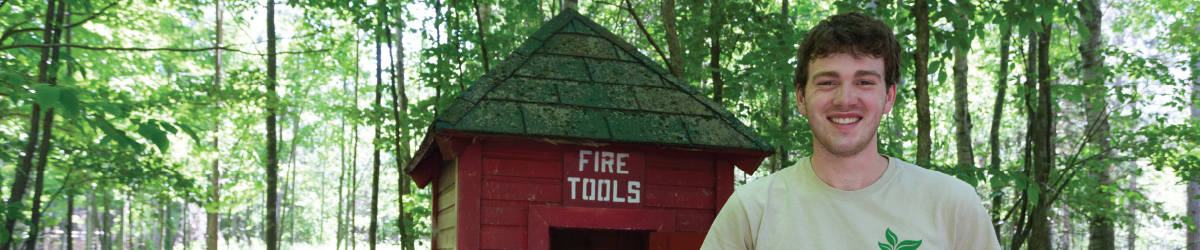 "A young man standing next to a ""fire tools"" shed in the forest."