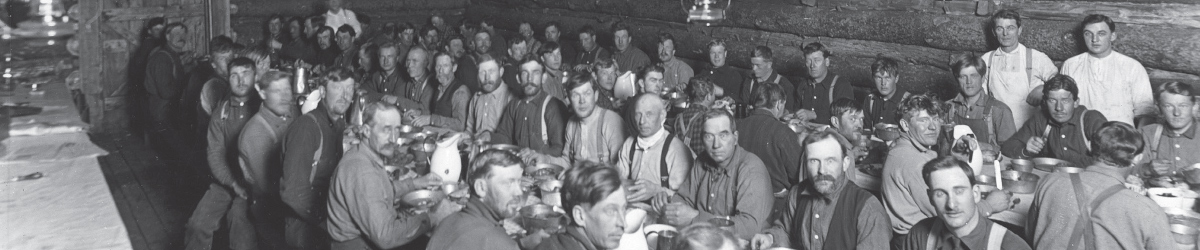 Lumberjacks sitting in front of long dining tables.