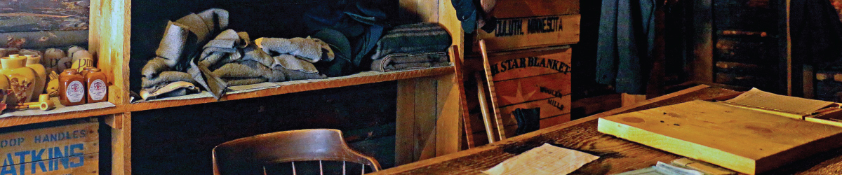 Old wood desk with display crates and products behind it.