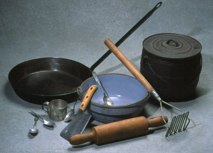 Color photo of lumber camp cooking tools: frying pan, bean pot, large bowl, potato masher, rolling pin, meat cleaver, measuring cup, and spoons.