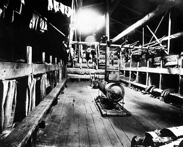 Photo of a bunkhouse interior at a lumber camp: a stove sits in the center, a rack hangs above it with clothes; bunk beds and benches (deacon seats) line the two walls, ca. 1910.
