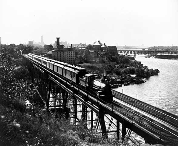 Photo of a train crossing the Mississippi River on a bridge near the University of Minnesota, 1900.