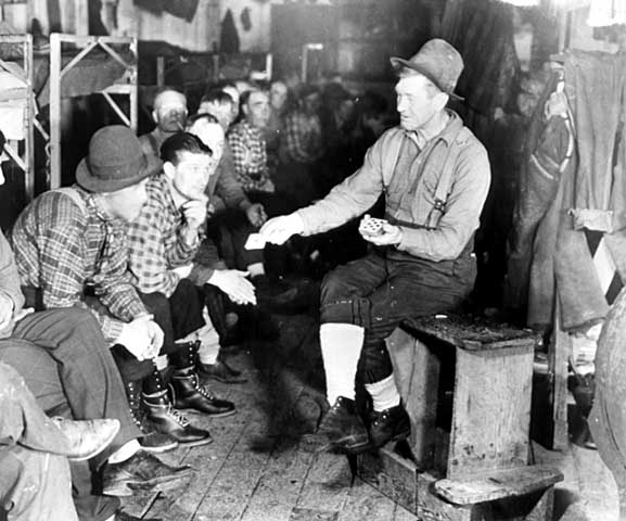 Photo of lumberjacks in a bunkhouse, one man is performing card tricks, ca. 1925.