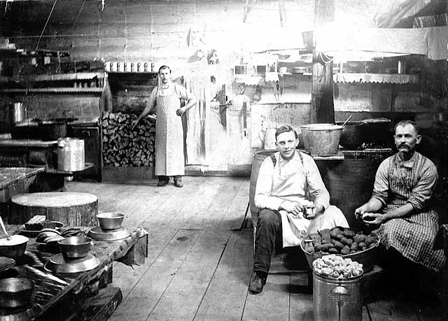 Photo of a lumber-camp kitchen, a male cook stands next to a pile of wood and two male cookees sit peeling potatoes, 1900.
