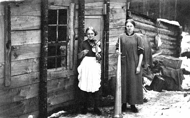 Photo of two female cooks; one holds a dinner horn and one holds a fiddle and both appear to be in their twenties, 1917.