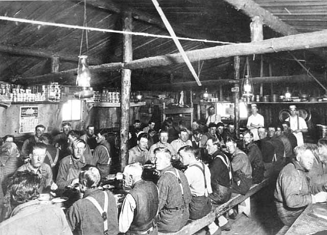 Photo of lumberjacks seated at three long tables in a log-structured cook shack with cooks standing in the background, 1900