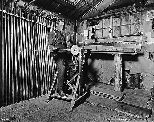Photo taken inside the filer's quarters of the filer sharpening a long saw with a foot-powered machine, 1914.