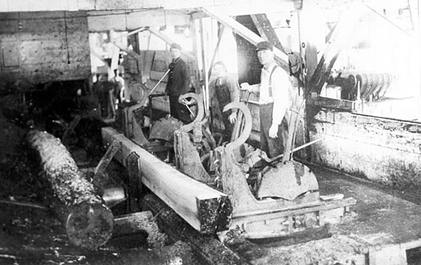 Photo of sawmill interior doggers and setters stand along a carriage that holds a cut log, ca. 1905.