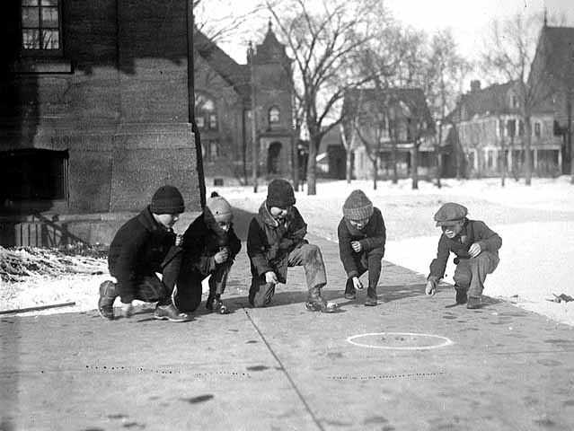 Photo of five young boys playing marbles on the sidewalk, ca. 1925.