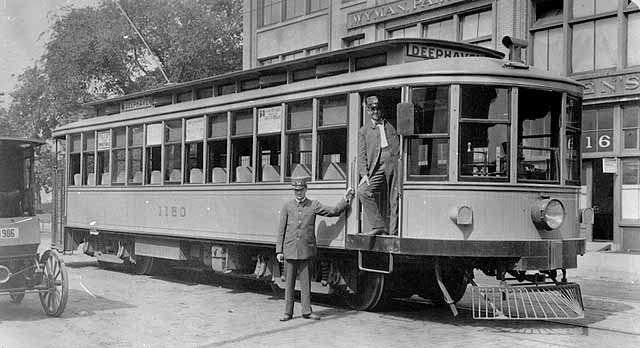 Photo of a streetcar during its layover, two conductors stand with it, Minneapolis, 1905.